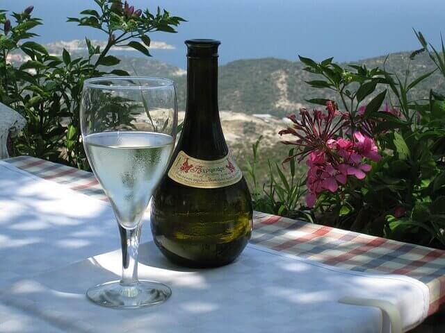 Bottiglia di vino retsina e calice pieno sul tavolo foto