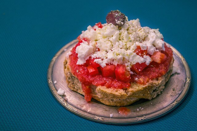 Un piatto con dakos, preparato con bruschetta di orzo condita con olio, sale, origano selvatico, pomodoro, formaggio feta e olive.